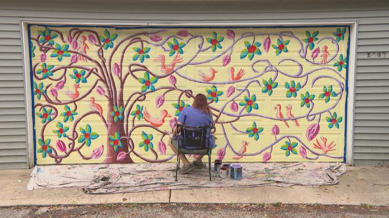 Evanston artist Teresa Parod paints a mural on a garage door. (WTTW News)