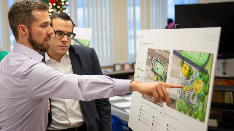 Project Manager Justin Rossman of Site Design Group explains the highlights of Ashe Elementary School's planned garden to Dean Alonistiotis, aide to MWRD Commissioner Kimberly Du Buclet. (Courtesy Metropolitan Water Reclamation District of Greater Chicago)