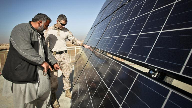 Maj. Erich Bergiel, right, inspects the solar panels on the roof of the Marjeh Fruit and Vegetable Packing Facility in Afghanistan while he talks with Abdul Rahman, a renewable energy engineer. (Master Gunnery Sgt. Phil Mehringer / U.S. Department of Defense)