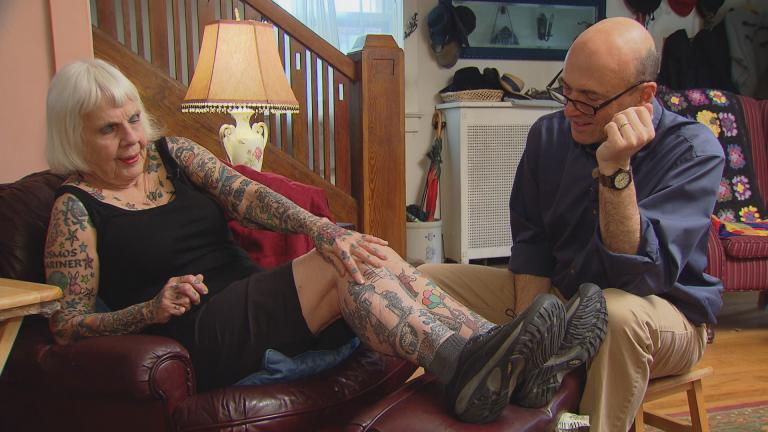 Helen Lambin shows Jay Shefsky her collection of tattoos.