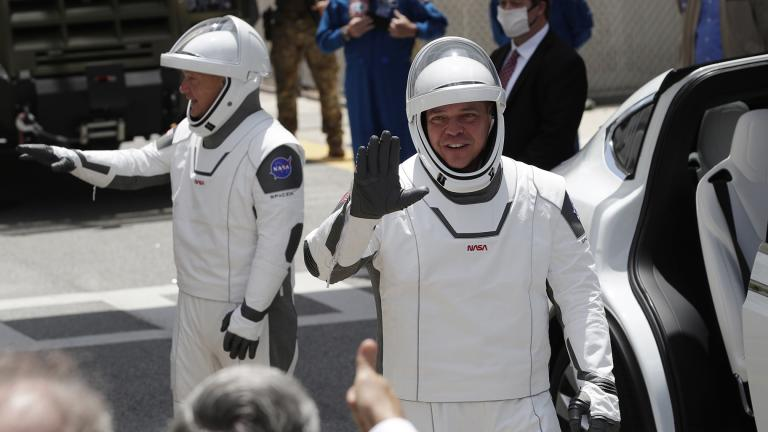 NASA astronauts Douglas Hurley, left, and Robert Behnken wave as they exit the Neil A. Armstrong Operations and Checkout Building on their way to Pad 39-A, at the Kennedy Space Center in Cape Canaveral, Fla., Saturday, May 30, 2020. (AP Photo / John Raoux)