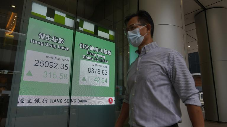 A man wearing a face mask walks past a bank electronic board showing the Hong Kong share index at Hong Kong Stock Exchange Tuesday, June 9, 2020. Asian shares were mixed on Tuesday after the Nasdaq hit a record high. (AP Photo / Vincent Yu)