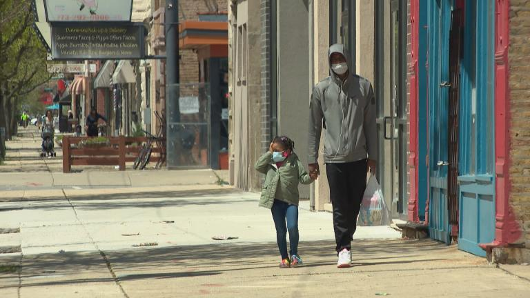 Family members wearing masks walk along the sidewalk in the Humboldt Park neighborhood on Thursday, May 7, 2020. Under Gov. J.B. Pritzker's stay-at-home order, all residents should wear face masks or coverings when social distancing is not possible. (WTTW News)