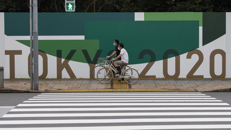 In this July 1, 2021, file photo, men cycle along the wall installed to close off a park being prepared for the Olympics and Paralympics Games in Tokyo. (AP Photo / Hiro Komae, File)