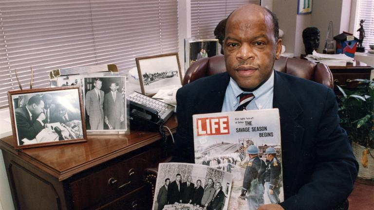 Congressman John Lewis is seen in his Atlanta office with two of his favorite items from his collection of memorabilia from his younger days as a civil rights activist in the 1960s. (Atlanta Journal-Constitution via AP)