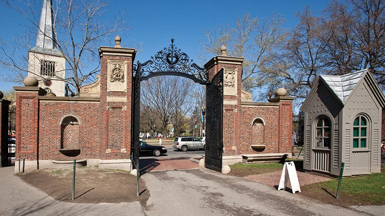 """The array of wrought iron atop Johnston Gate includes a wreath-adorned cross that symbolizes Harvard's early commitment to training ministers as well as numerals denoting the year of the university's founding, 1636. Above """"1636""""is a small shield displaying the year of the gate's completion, 1889. (Credit: Ralph Lieberman)"""
