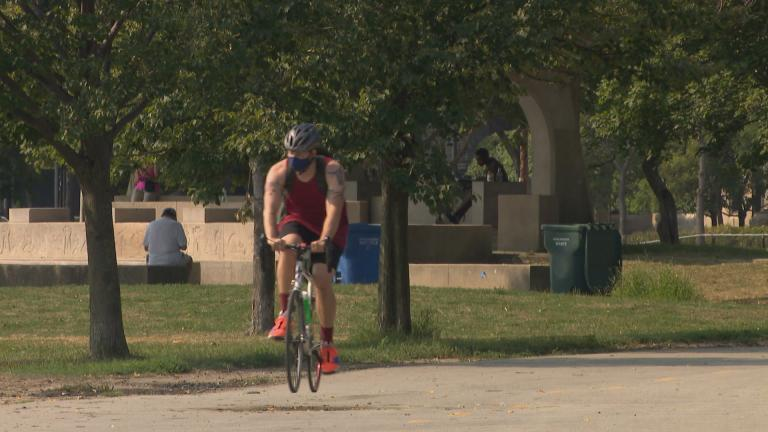 A cyclist wearing a mask rides along the lakefront trail in Chicago. (WTTW News)