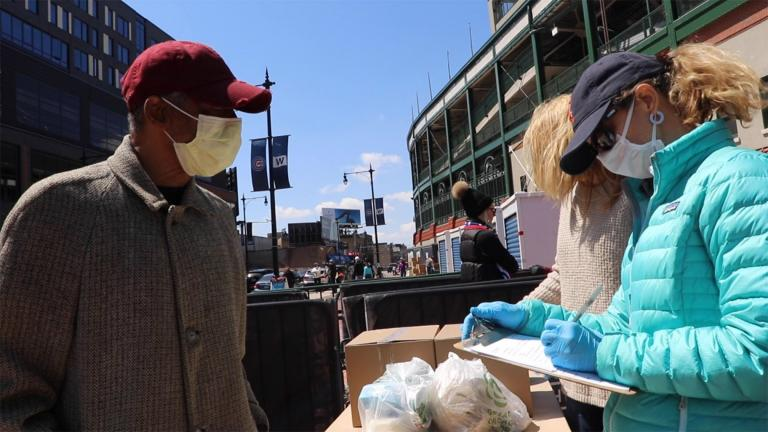 Wiley Alexander, of Chicago, speaks to Lakeview Food Pantry volunteers at Wrigley Field's temporary food pantry site on April 18, 2020. Alexander says he was laid off amid the COVID-19 pandemic. (Evan Garcia / WTTW News)