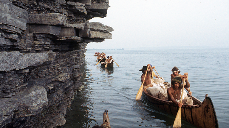 Paddling past a limestone spire on Lake Ontario, August 26, 1976. The canoe at the front contains Rich Gross, Bob Kulick, Reid Lewis, and John DiFulvio. (Photographers of the La Salle: Expedition II).