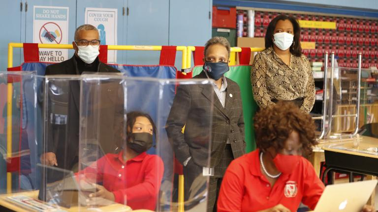 Chicago Mayor Lori Lightfoot, center, flanked by CPS CEO Janice Jackson (r) and Ald. William Burnett (l), listens to a class conference during their classroom tour on Feb. 11, 2021, at William H. Brown Elementary School. (AP Photo / Shafkat Anowar / Pool)