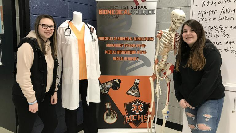 Sarah Touhy, left, a 2019 graduate of McHenry High School's East Campus and Breanna Darcy, a senior at McHenry High School's West Campus, pose for a picture on Jan. 15 in the biomedical science classroom at the east campus. (Courtesy of McHenry High School)