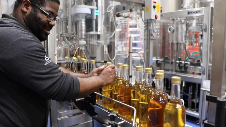 CH Distillery employee Nick White sends several bottles of Malort down the bottling production line. (Evan Garcia / WTTW News)