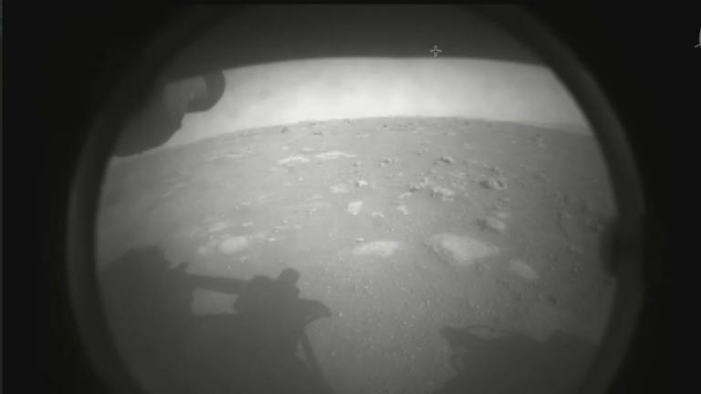 The first image NASA's Perseverance rover sent back after touching down on Mars on Feb. 18, 2021. The view, from one of Perseverance's Hazard Cameras, is partially obscured by a dust cover. (NASA / JPL-Caltech)