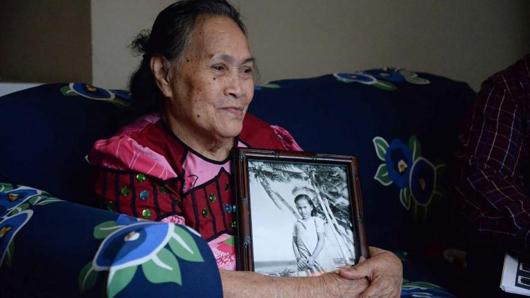 Mojina Jinuna Mote, holding a photo of herself taken in 1947. Mote's story is part of a new exhibit on the Marshall Islands at the Field Museum. (Courtesy of the Field Museum)