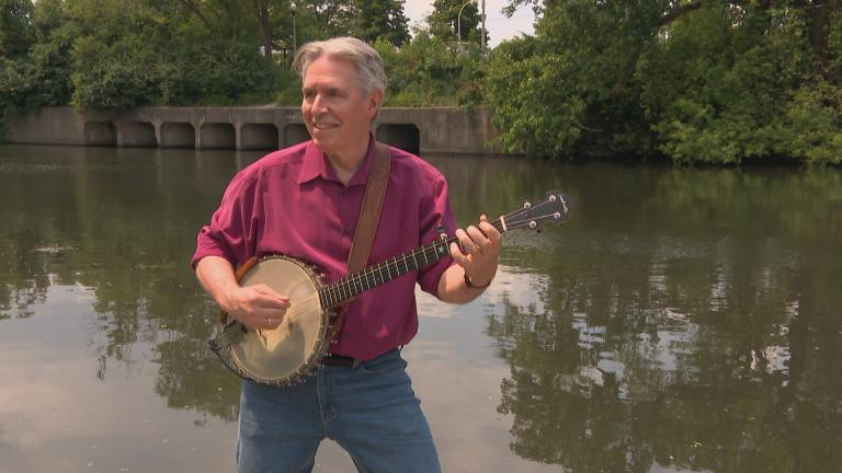 Michael Miles plays his banjo on the banks of the Chicago River. (WTTW News)