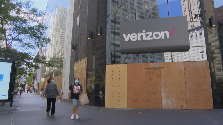 Shoppers walk past a string of boarded-up stores along Michigan Avenue on Friday, Aug. 28, 2020. Shopping along the retail-heavy strip and elsewhere in the city has taken a hit from the pandemic and also recent looting due to unrest. (WTTW News)