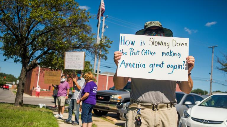Eric Severson holds a sign as a few dozen people gather in front of the United States Post Office on Rodd St. to protest recent changes to the U.S. Postal Service under new Postmaster General Louis DeJoy on Tuesday, Aug. 11, 2020 in Midland, Mich. (Katy Kildee / Midland Daily News via AP)