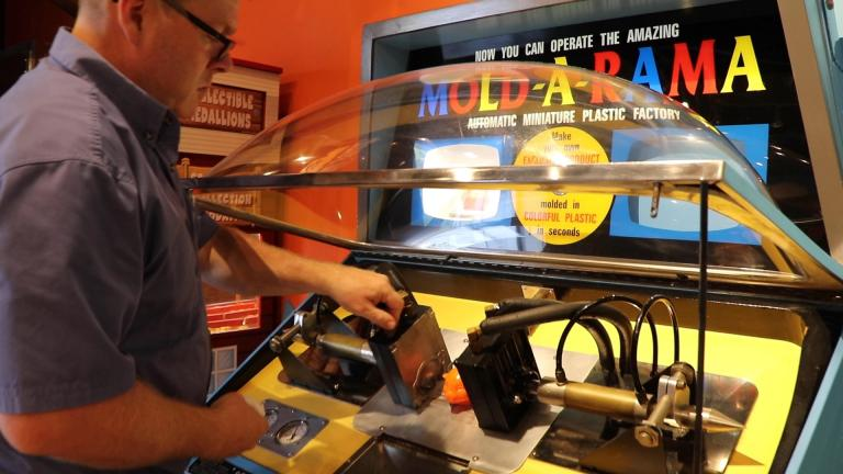 Paul Jones of Mold-A-Rama Inc. checks on a souvenir machine at Lincoln Park Zoo. (Evan Garcia / WTTW News)