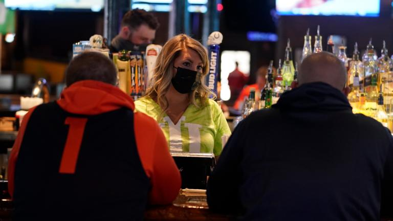 Jillian Smith takes an order from people at Kilroy's Bar & Grill, Sunday, March 14, 2021, in Indianapolis. (AP Photo / Darron Cummings)