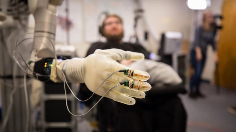 Nathan Copeland, who was paralyzed from the chest down in a car accident, controls a prosthetic arm and hand at the University of Pittsburgh Medical Center. (Photo courtesy of Pitt / UPMC)