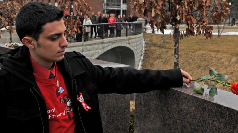 Patrick Korellis places a rose on the memorial at Northern Illinois University. (Courtesy of Patrick Korellis)