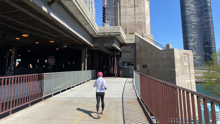 A runner approaches one of the Lake Shore Drive bridge houses on the nearly finished Navy Pier Flyover portion of the lakefront trail, April 30, 2021. (Nick Blumberg / WTTW News)