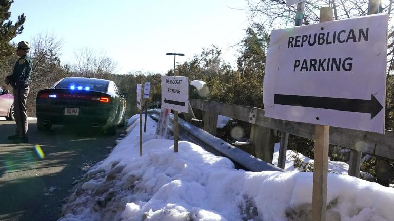 In this Feb. 24, 2021, file photo, a sign directs Republican and Democrat legislators to their parking areas as a N.H. State Trooper watches the flow of traffic prior to a New Hampshire House of Representatives session held at NH Sportsplex, due to the coronavirus in Bedford, N.H. (AP Photo / Charles Krupa, File)