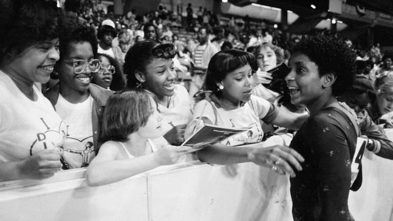 In this June 5, 1983, file photo, Dianne Durham, right, of Gary, Ind., gives autographs after winning the women's title at the McDonald's U.S.A. Gymnastic Championships at the University of Illinois in Chicago. (AP Photo / Lisa Genesen, File)