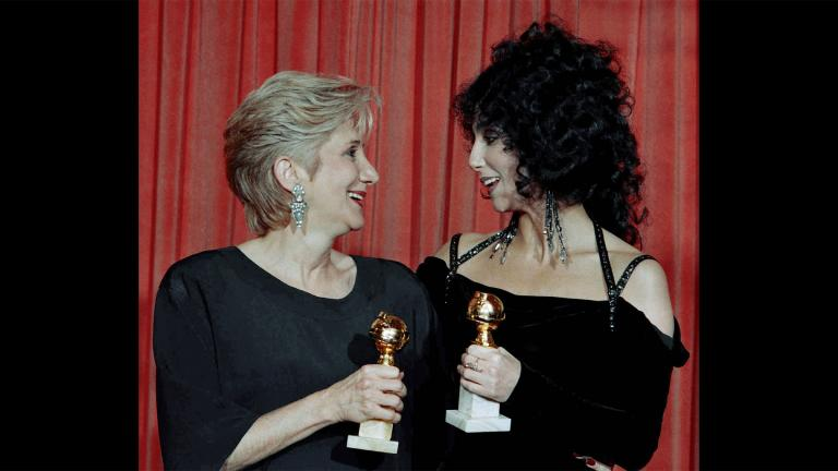 "In this Jan. 24, 1988 file photo, actress Olympia Dukakis, winner of a Golden Globe for ""Best Performance in a Supporting Role"" and Cher, winner of the ""Best Performance by an Actress in a musical or comedy,"" hold the awards they received for performances in the hit movie ""Moonstruck"" at the Beverly Hilton Hotel. (AP Photo / Reed Saxon, File)"