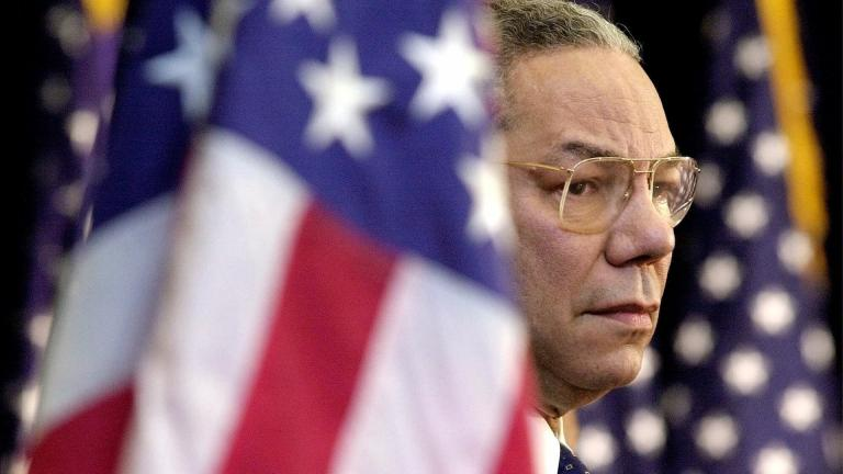 In this Feb. 15, 2001 file photo, Secretary of State Colin Powell looks on as President Bush addresses State Department employees at the State Department in Washington. (AP Photo/Kenneth Lambert)