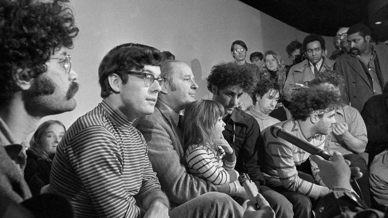 In this Feb. 28, 1970, file photo, the seven defendants in the Chicago Conspiracy Trial hold a press conference in Chicago after the 7th Circuit U.S. Court of Appeals granted their request for bail. Left to right, Lee Weiner, Rennie Davis, David Dellinger, Abbie Hoffman, Tom Hayden, (behind Hoffman), Jerry Rubin and John Froiners. Dellinger holds his granddaughter, Michelle Burd. (AP Photo / JLP, File)