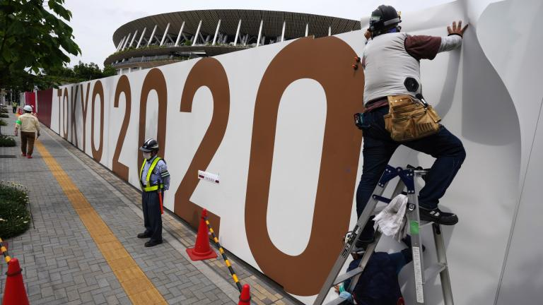 Workers paste the overlay on the wall of the National Stadium, where opening ceremony and many other events are scheduled for the postponed Tokyo 2020 Olympics, Wednesday, June 2, 2021, in Tokyo. (AP Photo / Eugene Hoshiko)