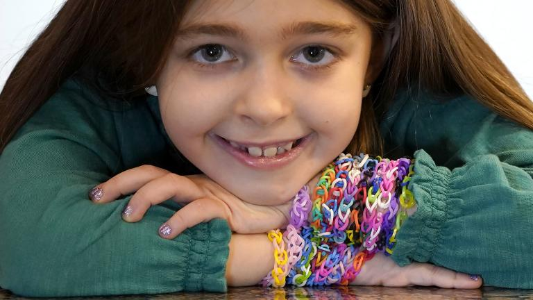 Hayley Orlinsky poses for a portrait Wednesday, Dec. 2, 2020, with several colorful rubber band bracelets she makes in her Chicago home. (AP Photo / Charles Rex Arbogast)