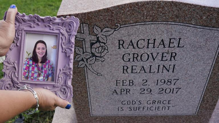 Sharon Grover holds up a photograph of her daughter, Rachael, over the gravesite at Fairview Cemetery, Tuesday, Sept. 28, 2021, in Mesopotamia, Ohio. Grover believes her daughter started using prescription painkillers around 2013 but missed any signs of her addiction as her daughter, the oldest of five children, remained distanced. (AP Photo / Tony Dejak)