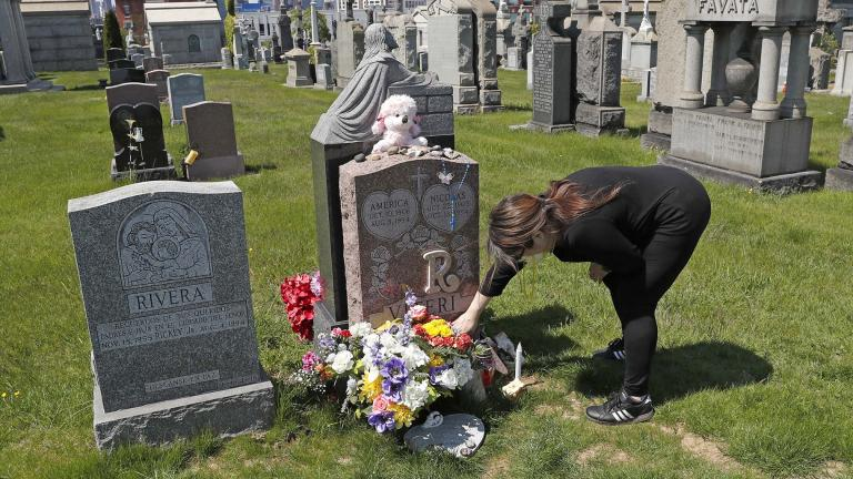 In this Sunday, May 10, 2020 file photo, Sharon Rivera adjusts flowers and other items left at the grave of her daughter, Victoria, at Calvary Cemetery in New York, on Mother's Day. (AP Photo / Kathy Willens, File)