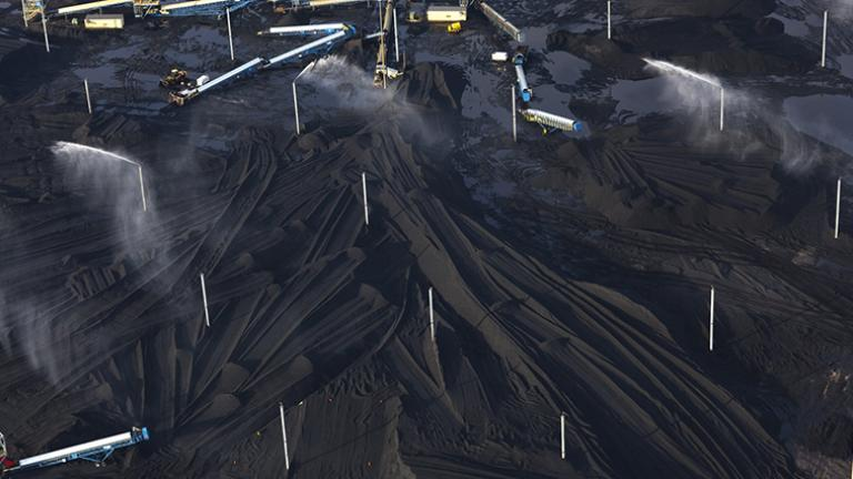 Petcoke piles with sprinklers at KCBX site on Calumet River, 2014. (Terry Evans / Courtesy of Museum of Contemporary Photography)