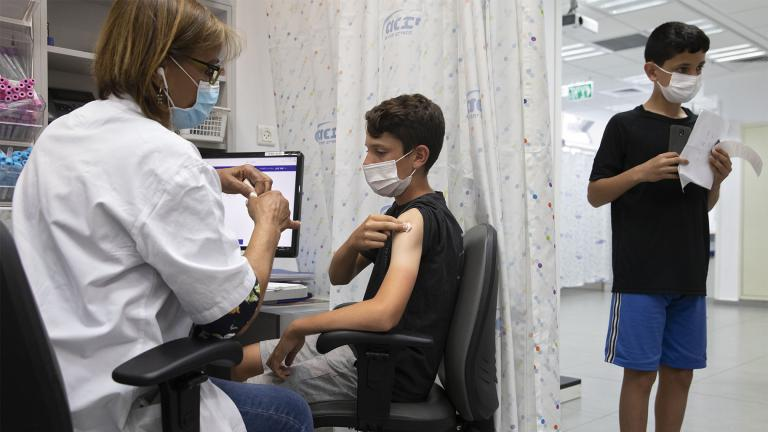 In this June 6, 2021 file photo, a youth receives a Pfizer-BioNTech COVID-19 vaccine in the central Israeli city of Rishon LeZion. (AP Photo / Sebastian Scheiner)