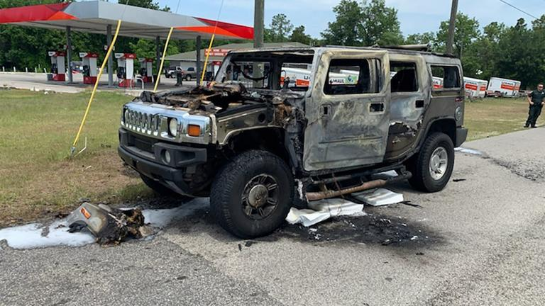 In this photo provided by Citrus County Fire Rescue an officer stands near a Hummer which was destroyed by fire shortly after the driver had filled up four 5-gallon (18-liter) gas containers on Wednesday, May 12, 2021, in Homosassa, Fla. (Citrus County Fire Rescue via AP)