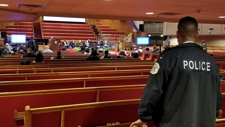 A Chicago police officer looks on during Monday's police board listening session at the Trinity United Church of Christ. (Matt Masterson / WTTW News)