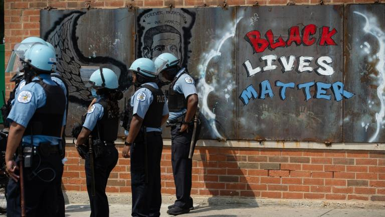 In this Aug. 15, 2020, file photo, police officers stand beside a mural for George Floyd in the Chicago neighborhood of Bronzeville during an anti-police brutality protest. (Pat Nabong / Chicago Sun-Times via AP, File)