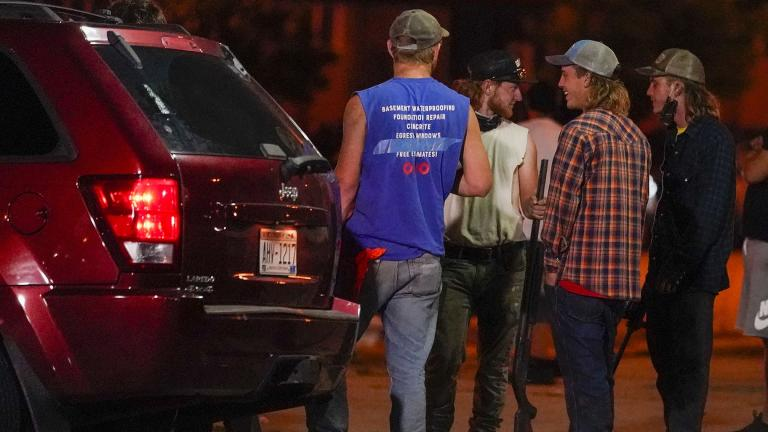A group holds rifles as they watch protesters on the street Tuesday, Aug. 25, 2020, in Kenosha, Wis. Protests continued following the police shooting of Jacob Blake two days earlier. (AP Photo / Morry Gash)