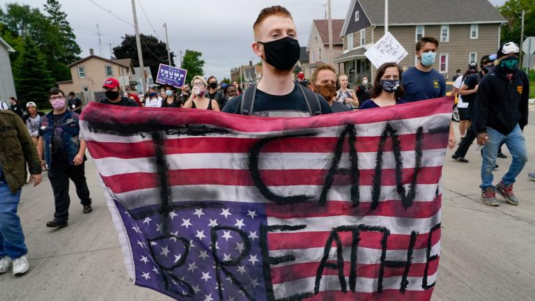 A protester holds a flag during a Black Lives Matter protest Tuesday, Sept. 1, 2020, in Kenosha, Wis. (AP Photo / Morry Gash)