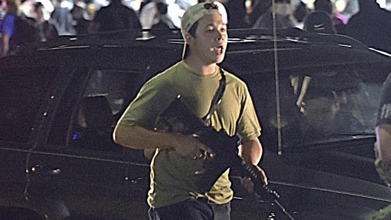In this Tuesday, Aug. 25, 2020 file photo, Kyle Rittenhouse carries a weapon as he walks along Sheridan Road in Kenosha, Wis., during a night of unrest following the weekend police shooting of Jacob Blake. (Adam Rogan/The Journal Times via AP, File)