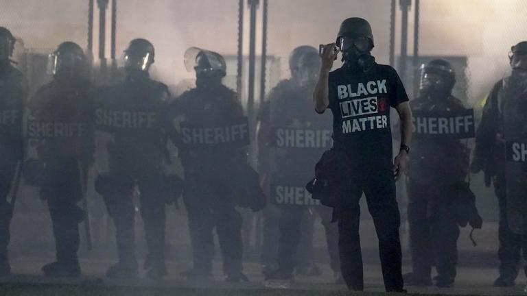 In this Aug. 25, 2020 file photo, a protester holds up a phone as he stands in front of authorities in Kenosha, Wis. (AP Photo/Morry Gash, File)