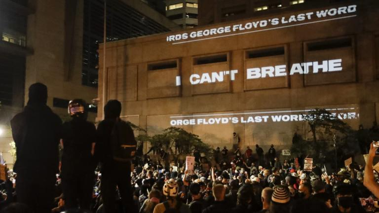 "In this Saturday, July 25, 2020, file photo, the words ""I can't breathe"" are flashed on a wall during a Black Lives Matter protest in Portland, Ore. (AP Photo/Marcio Jose Sanchez, File)"