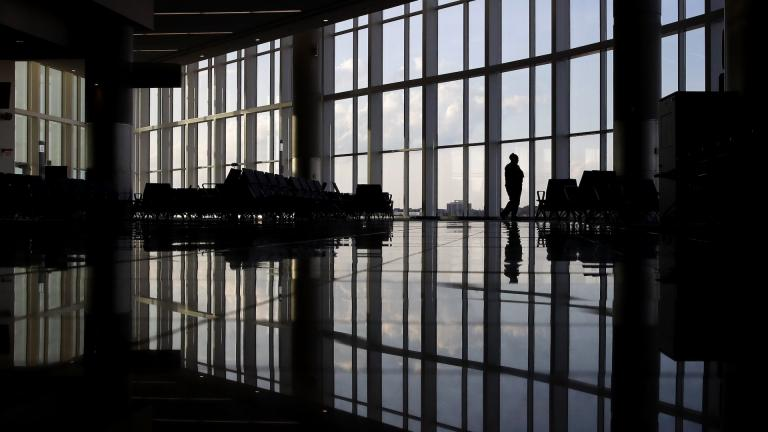 In this June 1, 2020 file photo, a woman looks through a window at a near-empty terminal at an airport in Atlanta. The coronavirus pandemic has taken a harsh toll on the mental health of young Americans, according to a new poll. (AP Photo/Charlie Riedel, File)