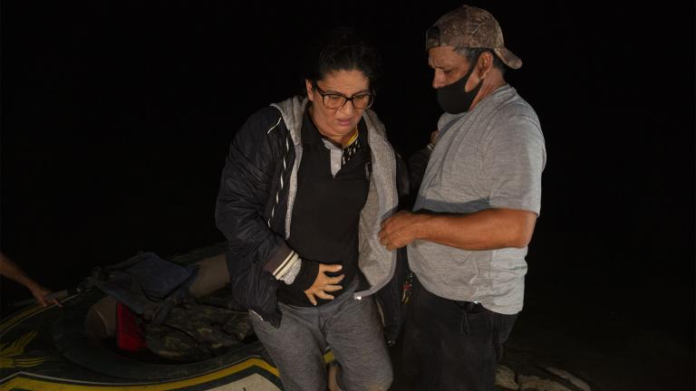 In this March 30, 2021, file photo Mayra Culio from Guatemala is helped off an inflatable raft by a church volunteer after being smuggled across the Rio Grande river in Roma, Texas. (AP Photo / Dario Lopez-Mills)