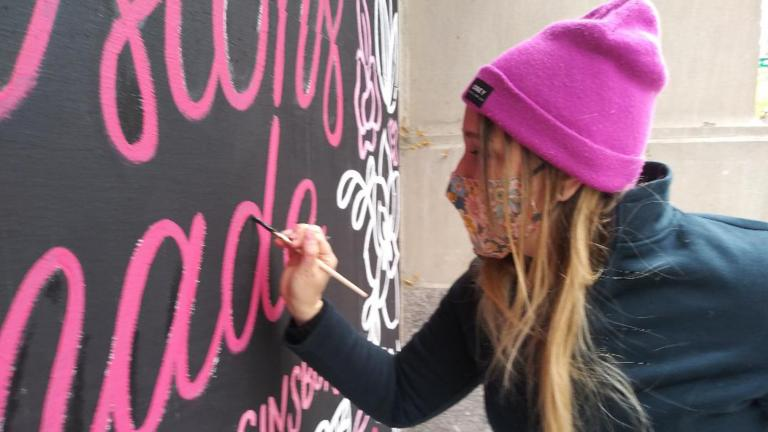 Artist Cristina Vanko hand-letters a Ruth Bader Ginsburg quote on a mural Sunday, Oct. 25, 2020. (Annemarie Mannion / WTTW News)