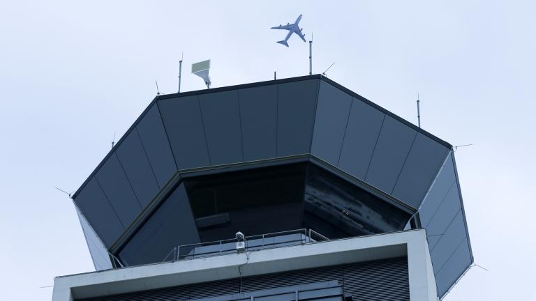 In this Monday, April 22, 2019 file photo, a plane flies over the south air traffic control tower at O'Hare International Airport in Chicago. (AP Photo / Kiichiro Sato, File)