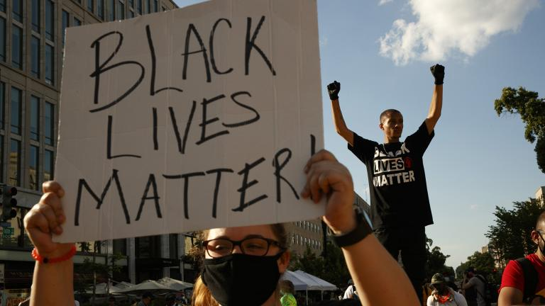 In this June 24, 2020, file photo, Antonio Mingo, right, holds his fists in the air as demonstrators protest in front of a police line on a section of 16th Street that's been renamed Black Lives Matter Plaza, in Washington. (AP Photo / Jacquelyn Martin, File)